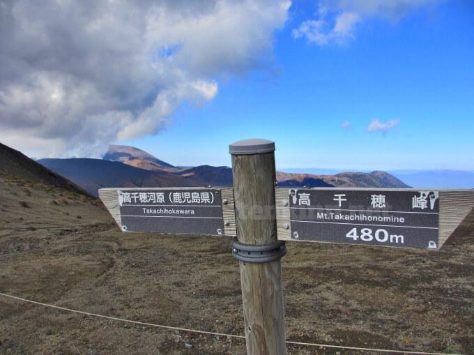24高千穂峰登山、背門丘の看板乃バックは新燃岳噴火中